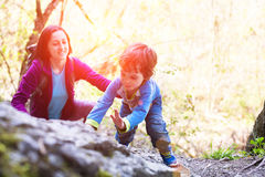 The child climbs on the boulder. A little boy climbs a big stone. Mom helps son to climb up Stock Image