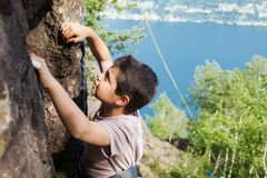 Child climbs on rock wall. Outdoor activities on a beautiful sunny day Stock Image