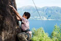Child climbs on rock wall. Outdoor activities on a beautiful sunny day with lake view Stock Photo