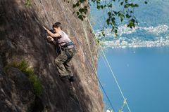 Child climbs on rock wall. Outdoor activities on a beautiful sunny day with lake view Stock Image