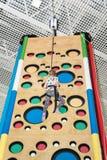Child climbs up the climbing wall Stock Image