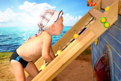 The child climbs up the ladder on the Playground on the beach in Sunny day. A little boy climbs on the ladder .Games on fresh air stock image