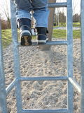 a child climbs up a ladder of a slide Royalty Free Stock Images
