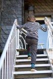 A child. Climbs up a metal ladder stock photo