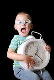 Child with clock. Cute boy with glasses holding a big clock isolated on a black background Royalty Free Stock Photo