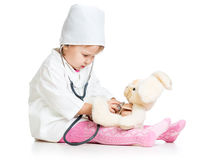 Child with clothes of doctor examining hare toy Royalty Free Stock Photos
