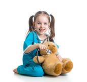 Child with clothes of doctor examining teddy bear. Adorable child with clothes of doctor examining teddy bear toy over white Royalty Free Stock Photos