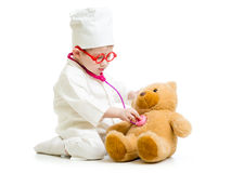 Child with clothes of doctor playing with toy Royalty Free Stock Image