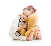 Child with clothes of doctor playing toy. Child with clothes of doctor playing plush toy Royalty Free Stock Images