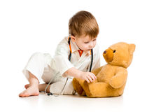 Child with clothes of doctor and teddy bear Royalty Free Stock Image
