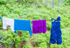 Child clothes on laundry line in woods Royalty Free Stock Photos