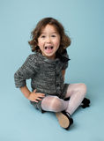 Child Clothing Fashion. Child and kids fashion and clothing: girl in modern outfit on blue background Stock Photo