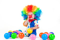 Child clown with a red nose multicolored wig in with balls Royalty Free Stock Photography