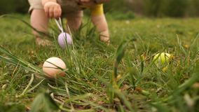 A child collects Easter eggs in the grass. Close-up, pens and legs. Happy easter family stock video footage