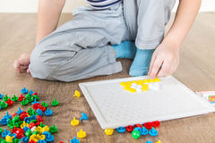 Child collects a puzzle. Child collects color puzzle in the room royalty free stock photo