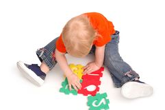 The child collects puzzles Royalty Free Stock Image