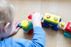 The child collects a toy wooden train. Stock Image