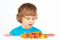Child with colored jelly candies on white background Stock Images