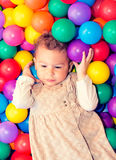 Child with colorful balls. A young girl child having fun playing with colorful plastic balls Royalty Free Stock Photos