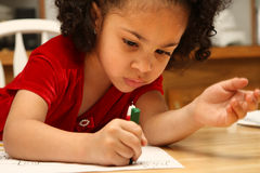 Child coloring. Beautiful multiracial child with afro hairstyle coloring a book stock photo