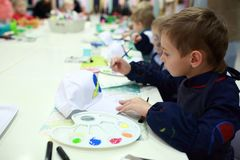 Child coloring baseball cap. Child coloring a baseball cap at table Royalty Free Stock Photo