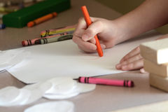 Child Coloring On Blank White Paper With Color Crayons Stock Photo