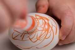 Coloring on an egg. A child coloring on a Easter egg Stock Images