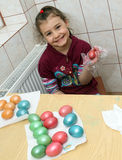 Child coloring easter eggs Royalty Free Stock Images