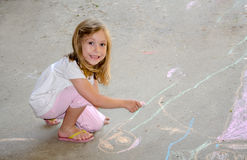 Child coloring with sidewalk chalk Stock Photography