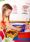 Child with colour pencil in play room. Stock Photography