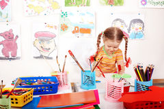 Child with colour pencil in play room. Royalty Free Stock Image