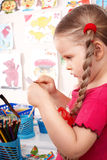 Child with colour pencil in play room. Stock Photo