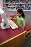 Child on Computer. Child in a school library stock photo