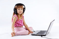 Child with computer. Portrait of funny modern child playing with computer and listening to music in headphones Stock Images