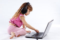 Child with computer. Portrait of funny modern child playing with computer and listening to music in headphones Royalty Free Stock Photography