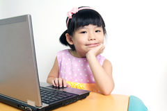 Child with computer. Little child girl is using laptop computer Royalty Free Stock Photography