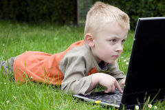 Child and computer. On the field Royalty Free Stock Photos