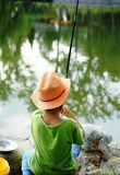 A child is concentrated on fishing on the bank Stock Photography