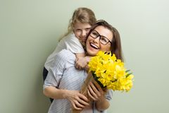 Child congratulates mother and gives her bouquet royalty free stock photo