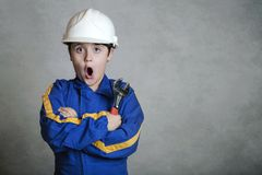 Child in construction uniform. Surprised child with a white helmet on gray background stock image