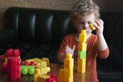Child with constructor. Little boy builds a tower from the constructor with concentration. He is curly-headed. The scene inside the room Royalty Free Stock Photography