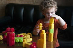 Child with constructor. Little boy builds a tower from the constructor with concentration. He is curly-headed. The scene inside the room. On the table scattered Royalty Free Stock Photography