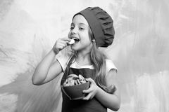 Girl chef or child cook in hat eating cookie food. Child cook or girl chef in hat eating cookie food on colorful background, copy space Stock Photography