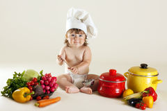 Child cook in surroundings vegetables and kitchen Royalty Free Stock Photo
