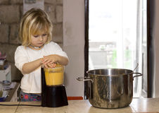 Child cooking. A young 4 year old girl is blending soup in a countryhouse farm kitchen, helping mummy to cook Royalty Free Stock Image