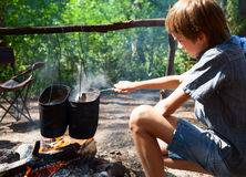 Child cooking on campfire Stock Photos
