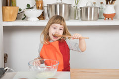Child cooking eating yogurt in wooden spoon. Three years old child with orange and red apron making and cooking a sponge cake at kitchen home, eating yogurt with Royalty Free Stock Photography