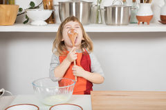 Child cooking licking yogurt in wooden spoon. Funny three years old child with orange and red apron making and cooking a sponge cake at kitchen home, licking Royalty Free Stock Image