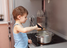Child cooking porridge Stock Photo