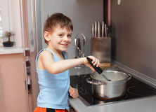 Child cooking porridge Stock Photos